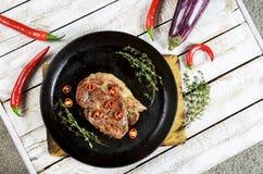 Carne con las especias en una cacerola, un romero, y pimientas del chile picante en un fondo de madera blanco de la tabla Foto de archivo libre de regalías
