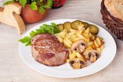 Carne con las patatas fritas y las salmueras Fotografía de archivo libre de regalías