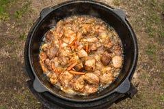 Carne con las zanahorias y la cebolla en caldera en el fuego Imagen de archivo