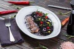Carne con un adorno en la placa blanca cordero con la cebada de perla con tinta de las jibias Cocina del este Fotos de archivo libres de regalías