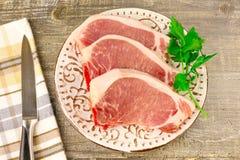 Carne cortada crua da placa branca na tabela de madeira, vista superior Alimento, uma faca, ramos dos verdes Imagens de Stock Royalty Free