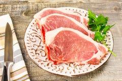 Carne cortada crua da placa branca na tabela de madeira, vista superior Alimento, uma faca, ramos dos verdes Fotografia de Stock