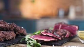 Carne cortada de la carne asada en un soporte negro Ase la carne para las hamburguesas Ponga verde las hojas de menta condimento  almacen de metraje de vídeo