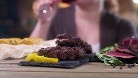 Carne cortada de la carne asada en un soporte negro Ase la carne para las hamburguesas Ponga verde las hojas de menta Pimienta am almacen de video