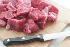 Carne cortada en cuadritos en la tarjeta de corte Fotos de archivo