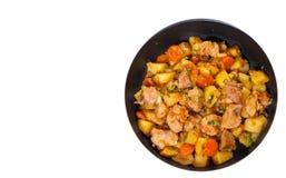 Carne cozido com batatas, cebola e cenoura em uma frigideira Vista superior Isolado Imagem de Stock