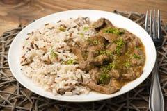Carne cozido e arroz na placa branca no fundo de madeira Fotografia de Stock