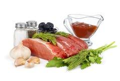 Carne cru: reforço e faixa frescos de carne de porco cru da carne prontos ao cozimento com alho e material verde Foto de Stock
