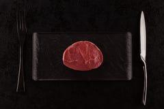 Carne crua, bife no fundo preto, vista superior Imagens de Stock