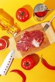 Carne crua da carne em uma placa de madeira e em ingredientes para cozinhar em um fundo amarelo fotografia de stock royalty free