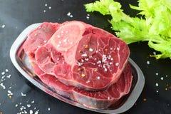 Carne crua da vitela com osso A carne de Ossobuco em uma bandeja do metal em um fundo abstrato cinzento com algum aipo fresco ver Imagem de Stock