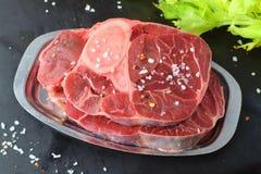 Carne crua da vitela com osso A carne de Ossobuco em uma bandeja do metal em um fundo abstrato cinzento com algum aipo fresco ver Fotos de Stock