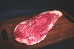 Carne crua do flanco em uma placa de madeira fotos de stock royalty free