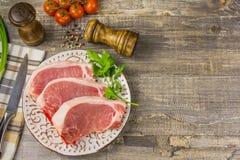Carne crua em uma placa com verdes, pimenta, folha de louro, conceito de madeira do guardanapo de tabela da faca de cozinha da es Foto de Stock