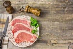 Carne crua em uma placa com verdes, pimenta, folha de louro, conceito de madeira do guardanapo de tabela da faca de cozinha da es Imagens de Stock Royalty Free