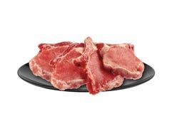 Carne crua: a faixa fresca da carne de porco da carne remenda na placa isolada Foto de Stock