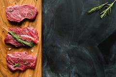 Carne crua fresca na placa de desbastamento com alecrins Parte-vista Imagens de Stock Royalty Free