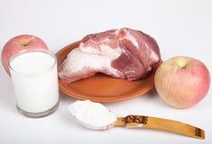 Carne crua, maçãs, farinha e um vidro do leite Ainda vida no branco Fotografia de Stock