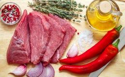 Carne crua, vegetais e especiarias Carne fresca, pimentas, cebola vermelha, alho, tomilho, azeite Imagens de Stock