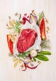 Carne cruda, componiendo con las hierbas, especias y sazonando en el fondo de madera blanco, ingredientes para cocinar Fotos de archivo libres de regalías