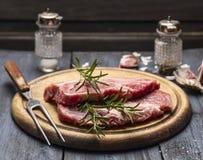 Carne cruda con i rosmarini, l'aglio, il sale ed il pepe su un bordo di legno con una forcella fotografie stock libere da diritti
