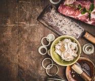 Carne cruda con il macellaio Cleaver e gli ingredienti per carne che griglia sul fondo di legno rustico fotografia stock libera da diritti