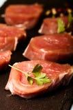 Carne cruda con las hierbas y las especias en una placa negra de la pizarra en un azul Fotos de archivo