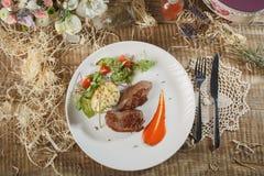 Carne cruda con le erbe, i condimenti, la ciliegia del pomodoro, i cetrioli e la crema bianca del souce sulla tavola rotonda di l Immagine Stock Libera da Diritti