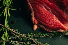 Carne cruda de la carne de vaca con las especias en tablero de la cocina de la piedra de la pizarra Foto de archivo
