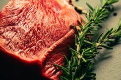 Carne cruda de la carne de vaca con las especias en tablero de la cocina de la piedra de la pizarra Foto de archivo libre de regalías