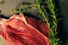 Carne cruda de la carne de vaca con las especias en tablero de la cocina de la piedra de la pizarra Imagen de archivo libre de regalías