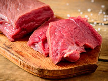 Carne cruda de la carne de vaca en tabla de cortar de madera rústica Fotografía de archivo libre de regalías