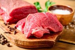 Carne cruda de la carne de vaca en tabla de cortar de madera rústica Imagen de archivo