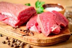 Carne cruda de la carne de vaca en tabla de cortar de madera rústica Imagenes de archivo
