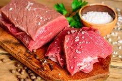 Carne cruda de la carne de vaca en tabla de cortar de madera rústica Fotos de archivo libres de regalías