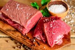 Carne cruda de la carne de vaca en tabla de cortar de madera rústica Fotografía de archivo