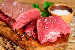 Carne cruda de la carne de vaca en tabla de cortar de madera rústica Imagen de archivo libre de regalías