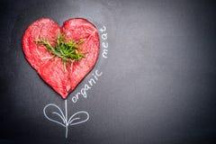 Carne cruda de la forma del corazón con las hierbas con la inscripción orgánica pintada de la carne alrededor Fondo oscuro de la  Fotografía de archivo libre de regalías
