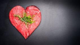 Carne cruda de la forma del corazón con las hierbas en fondo oscuro de la pizarra Forma de vida o concepto sana del alimento biol Fotos de archivo