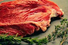 Carne cruda de la carne de vaca con las especias en tablero de la cocina de la piedra de la pizarra Fotos de archivo