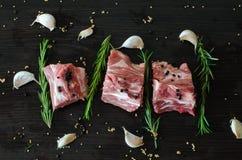 Carne cruda del cerdo con los huesos y el romero imágenes de archivo libres de regalías