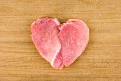 Carne cruda en la forma de un corazón imagenes de archivo