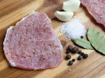 Carne cruda en una tabla de cortar de madera con las especias Fotos de archivo