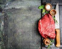 Carne cruda fresca con las hierbas, las especias y el cuchillo de carnicero en el fondo rústico, visión superior, lugar para el t Imagen de archivo