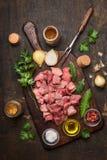 Carne cruda per la preparazione del goulash con petrolio ed erbe e spezie fresche su fondo di legno rustico immagini stock