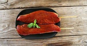 Carne cruda sesgada adornada con albahaca almacen de metraje de vídeo