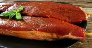 Carne cruda sesgada adornada con albahaca almacen de video