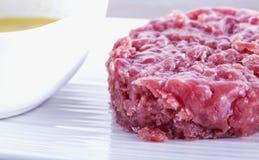 Carne cruda sobre la placa blanca Foto de archivo libre de regalías