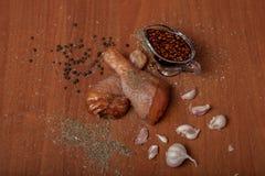 Carne cruda su un truciolato di legno, spezie del pollo per il pollo, sale, romano, basilico, aglio, pepe, salsa di soia su un ba Fotografia Stock