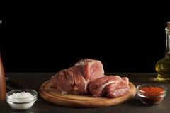 Carne cruda sul fondo scuro del ot del tagliere pronto alla cottura fotografia stock